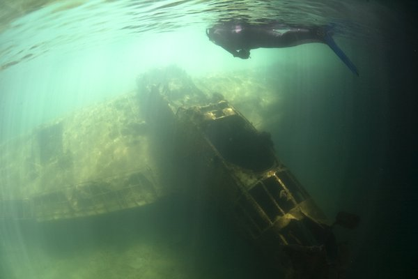 A snorkeler looks down upon a Japanese seaplane that was sunk in a shallow lagoon during WWII in Palau. thumbnail