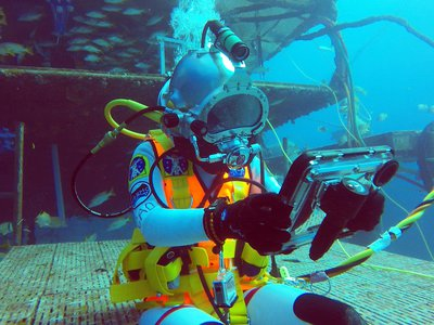 Csilla Ari D'Agostino sits in front of the Aquarius habitat and uses a waterproof iPad for cognitive tests as part of her research on NEEMO 23.