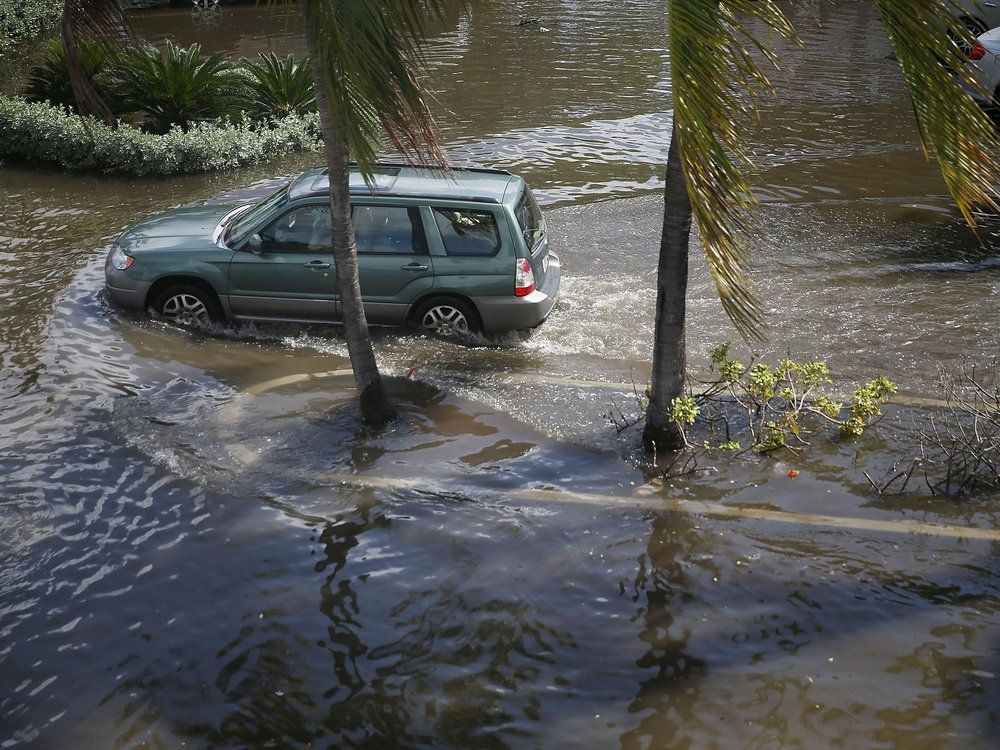 A vehicle drives through flooded streets caused by the combination of the lunar orbit which caused seasonal high tides and what many believe is the rising sea levels due to climate change on September 30, 2015 in Fort Lauderdale, Florida