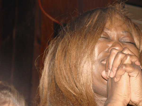 A woman prays, full of emotion, while watching President Obama's inauguration. thumbnail