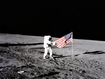 """Charles """"Pete"""" Conrad stands with the United States flag on the lunar surface on November 19, 1969."""