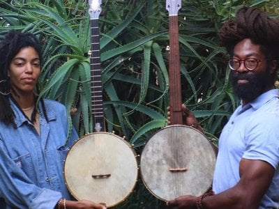 """Black Banjo Reclamation Project founders Hannah Mayree and Carlton """"Seemore Love"""" Dorsey, with banjos made by Brooks Masten of Brooks Banjos in Portland, Oregon. (Photo by Avé-Ameenah Long)"""