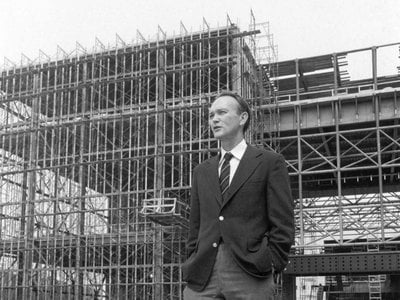 Michael Collins, the Museum's third director, stands before the steel skeleton of the new National Air and Space Museum in July 1974.