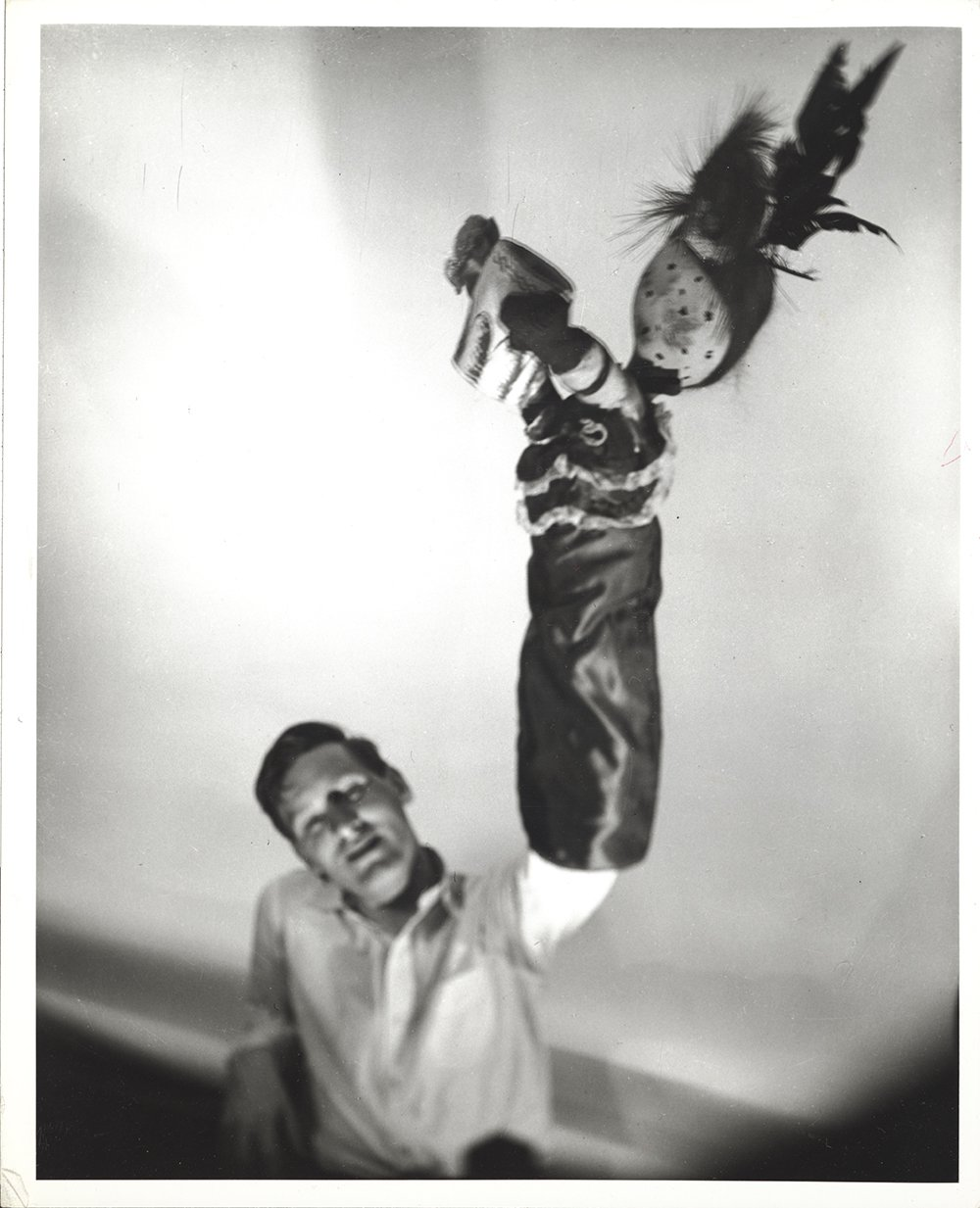 Blurry black and white photo of a man sitting in a chair wearing a white shirt and holding up a large puppet that resembles a bird.