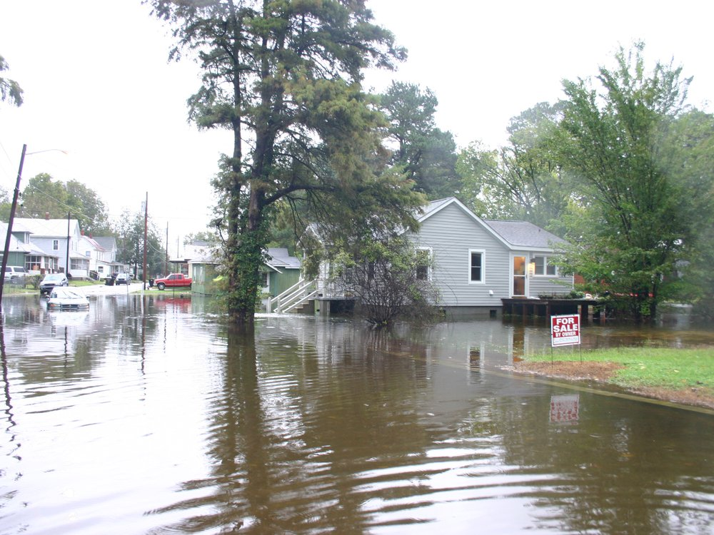 """Image of a flooded neighborhood in North Carolina. The street is flooded with water and a car is halfway stuck in it. The water comes up to the houses' front porches. A """"FOR SALE BY OWNER"""" sign is in a front yard."""