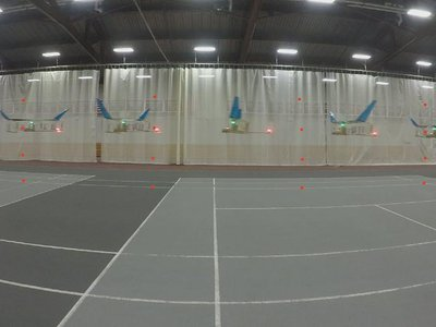 A time-lapse image showing the plane flying across a gymnasium.
