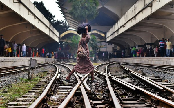 A man crossing the rail lines to go from one side to another. thumbnail