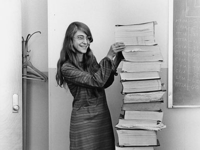 Margaret Hamilton stands next to a stack of program listings from the Apollo Guidance Computer in a photograph taken in 1969.