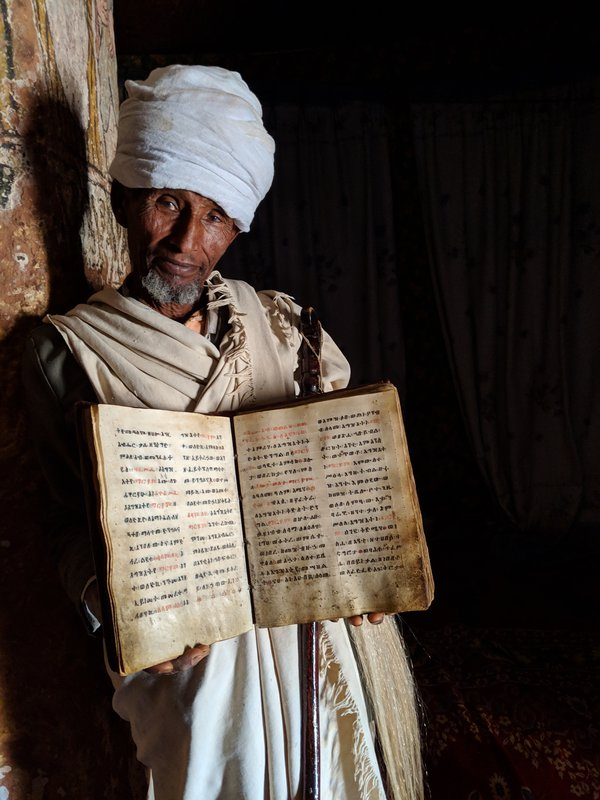 African priest holding bible thumbnail