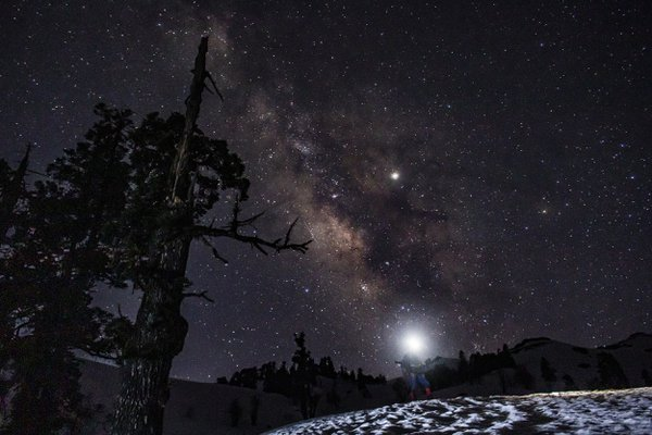 A trek guide poses for a photo with the milky way as the backdrop. thumbnail
