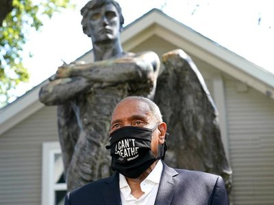 The museum's CEO emeritus, John Guess Jr., stands in front of the newly installed Spirit of the Confederacy sculpture.