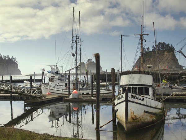 Sea stacks dwarf fishing boats in clearing fog in the remote tribal village of La Push, Washington. thumbnail