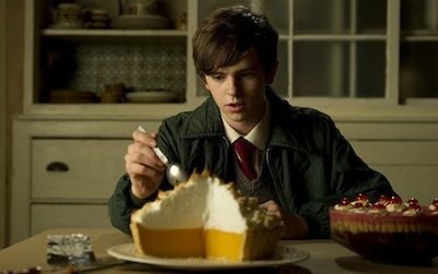 Nigel Slater, played by Freddie Highmore, digs into his stepmother's lemon meringue pie while his own trifle sits on the sidelines.