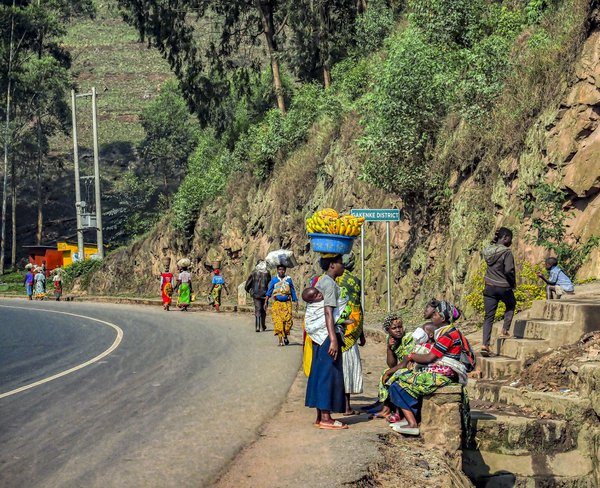 Woman carrying bananas on her head and a baby on her back stops to talk along the road in Gakenke District, Rwanda. thumbnail