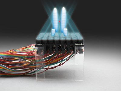 An artist's rendering shows an acoustic hologram trapping a particle over a levitation device.