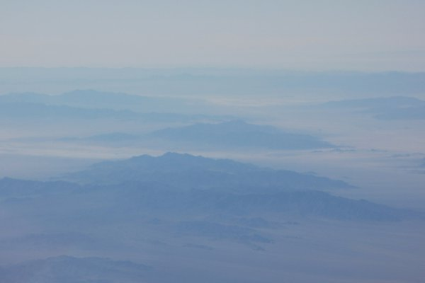 The Sierra Nevada mountains peek through a bluish November fog. thumbnail
