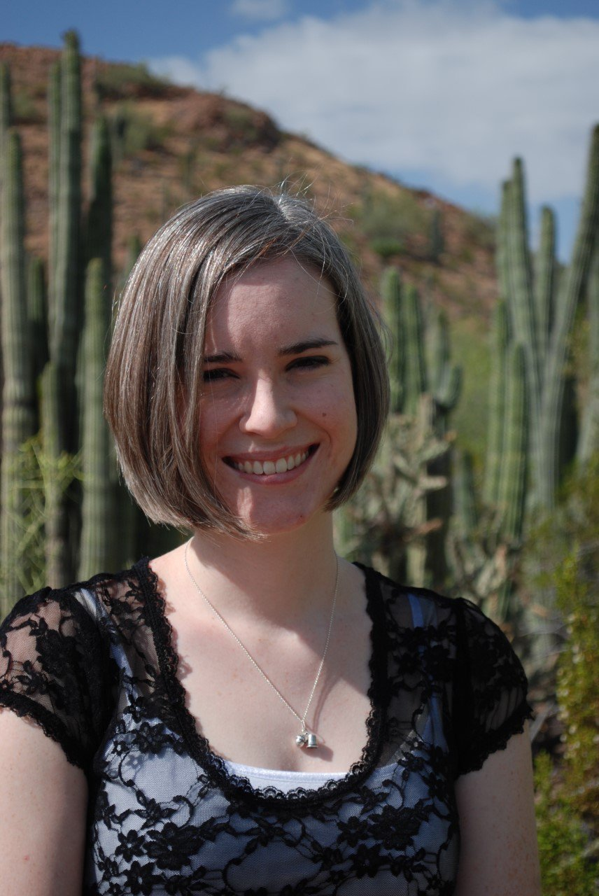 A person in front of cacti.