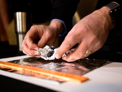 Astronomer Todd Slisher unfolds tin-foil to reveal a piece of stony-iron meteorite during a press conference, Friday, January 19, 2018, at the Longway Planetarium in Flint, Michigan.