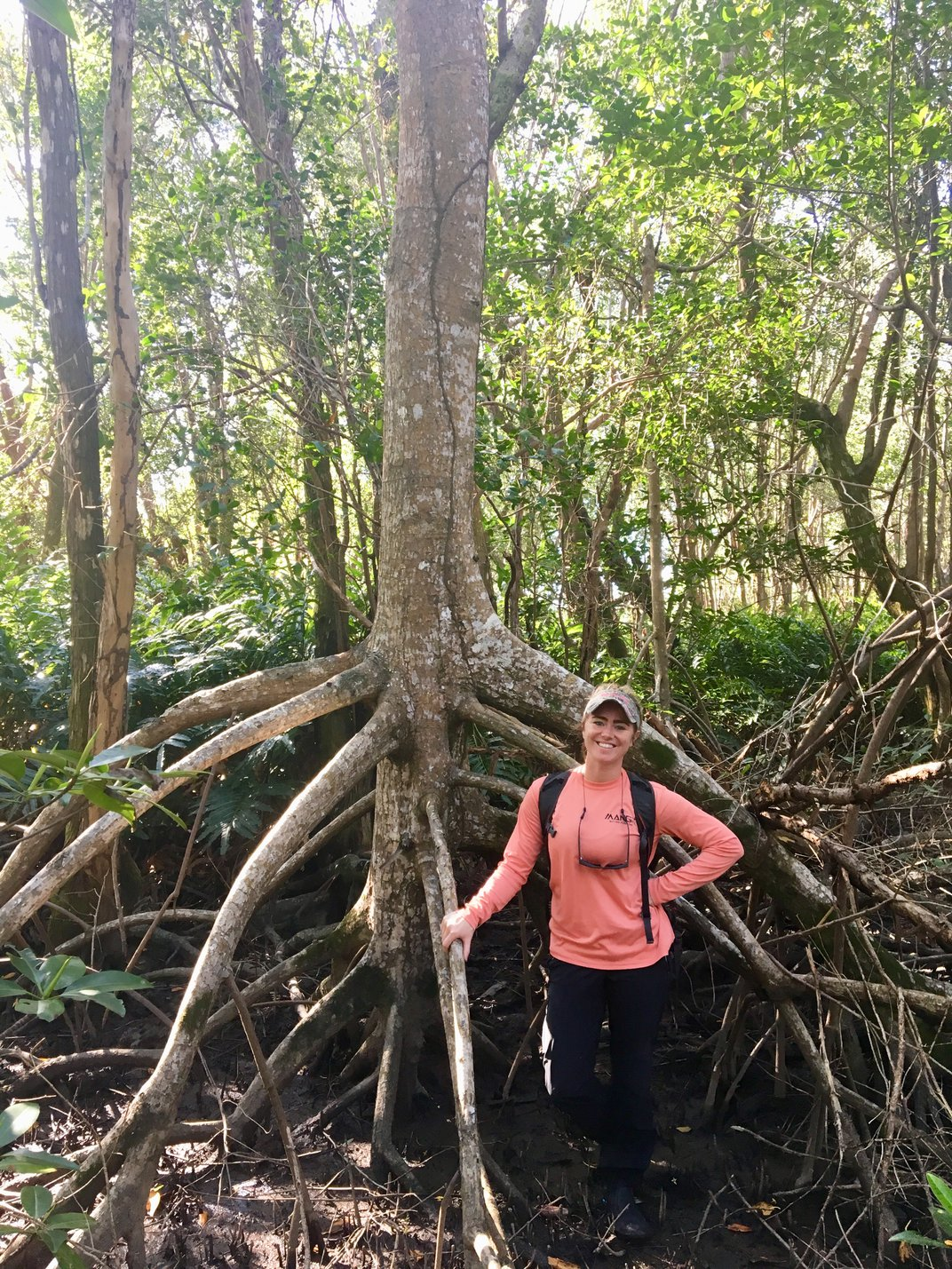 A person in front of a mangrove tree.