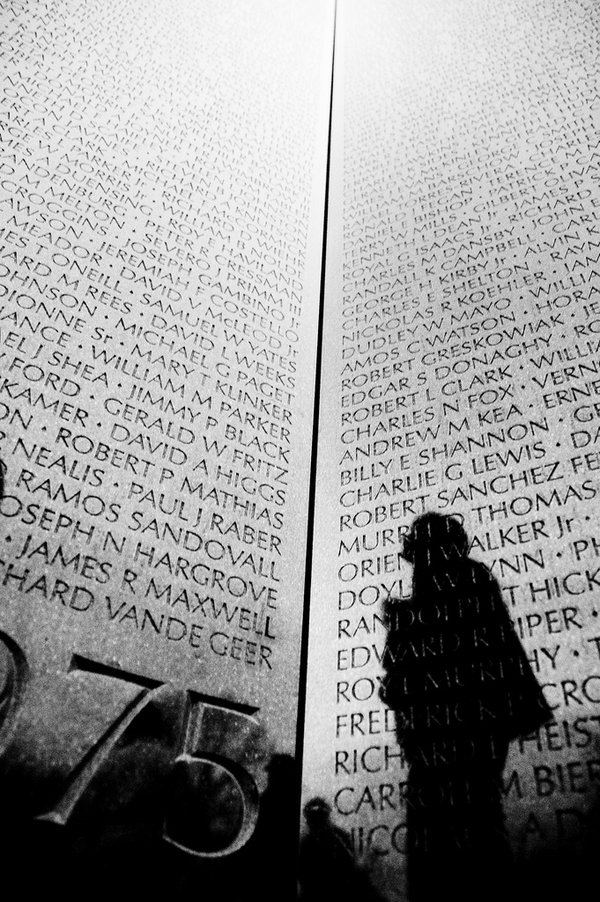 A silhouetted figure looks up at the Vietnam Memorial in Washington, DC. thumbnail