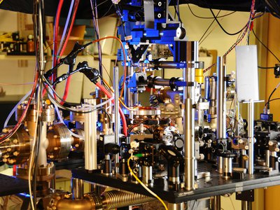 This is an atomic clock that uses the predictable frequency of ytterbium atoms absorbing and emitting light to tell time. A new experiment paired a ytterbium-based atomic clock with two others that used aluminum and strontium atoms, respectively, to create an even more accurate measure of time.
