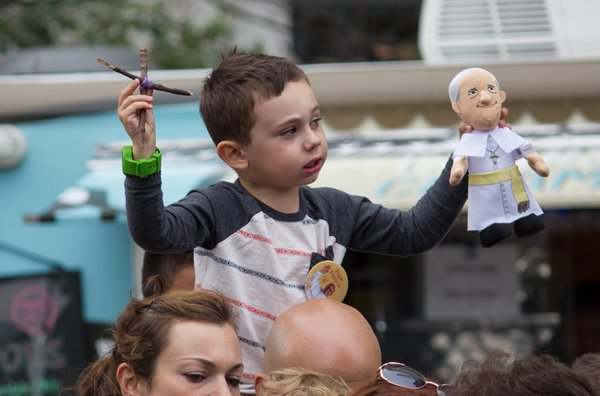 A boy on top of his father's shoulders during Papal mass in Philadelphia. thumbnail