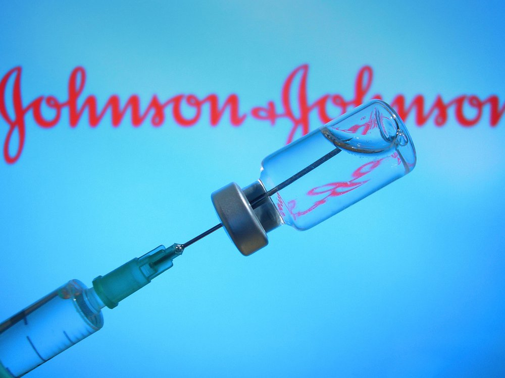 A vaccine is held up in front of a screen with the Johnson & Johnson logo