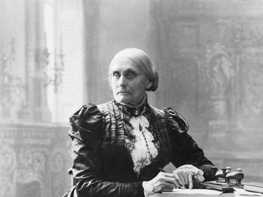 A black and white photograph of a woman with a tight bun, wearing a ruffled black dress with a white neckpiece, sitting a desk and in the middle of writing a letter, not smiling