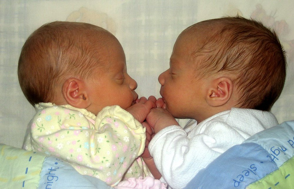 A photo of two newborns facing each other and holding hands