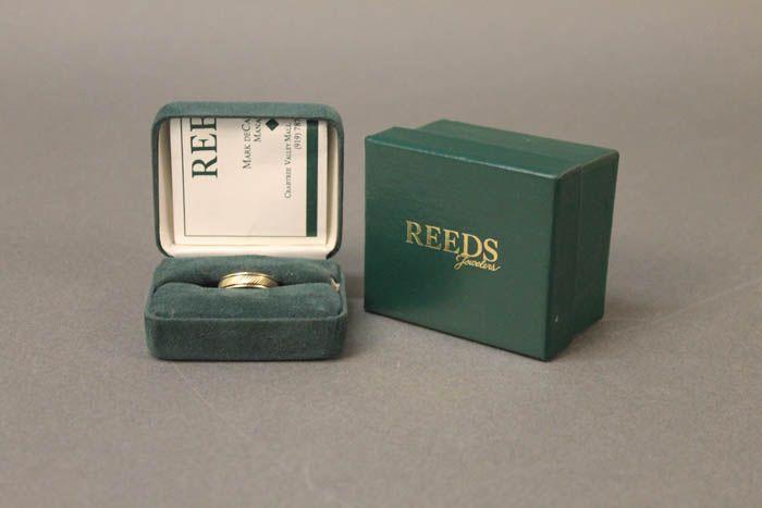 Gold wedding band in dark green ring box