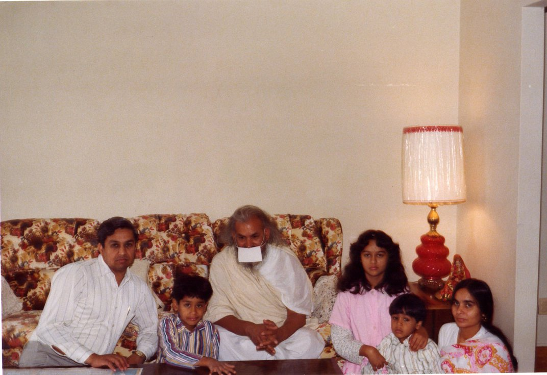 Old family photo with the Jain family and an older man posing, sitting on and around a beige floral-patterned couch. The older man is wearing a white face mask.