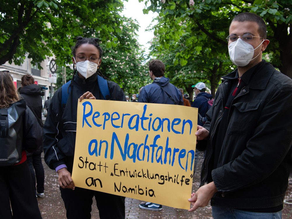 Two people in masks hold a yellow sign with blue and black handpainted letters, standing in a city street in front of trees and other protesters