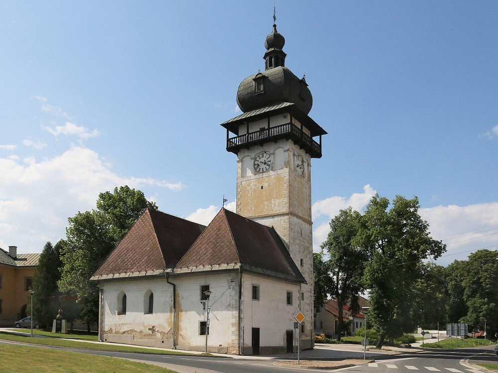 One tall tower with a domed black roof, next to two small buildings