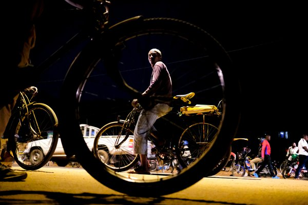 Pascal Itangishaka, a bicycle taxi rider, on the look out for passengers at a bus stop in Kigali, Rwanda. thumbnail