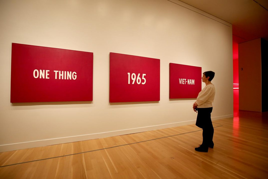 """A photograph of a woman standing in front of a three panel painting that has words that say, """"On thing, 1965, Viet-nam."""""""