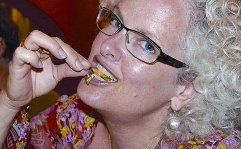 Janice Waugh eating a cricket on the Riviera Maya, Mexico
