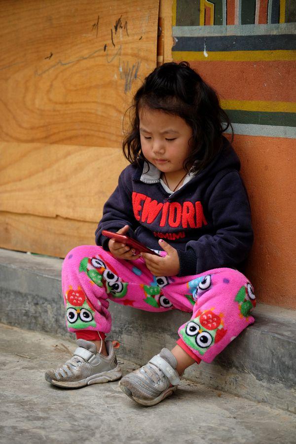 A young Bhutanese Girl playing on her handphone thumbnail