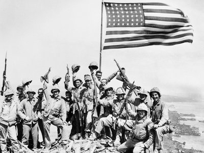 United States Marines pose on top of Mount Suribachi on the island of Iwo Jima with the American flag on February 23, 1945.
