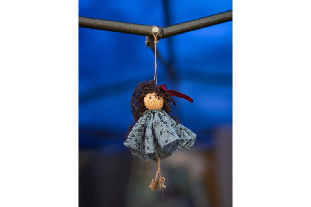 Hanging from a string is a small wooden doll with curly brown hair, outfitted in a blue dress.
