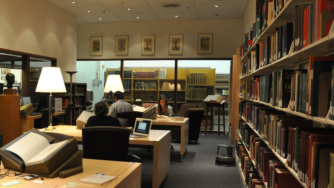 Photo of library reading room with several readers at desks.