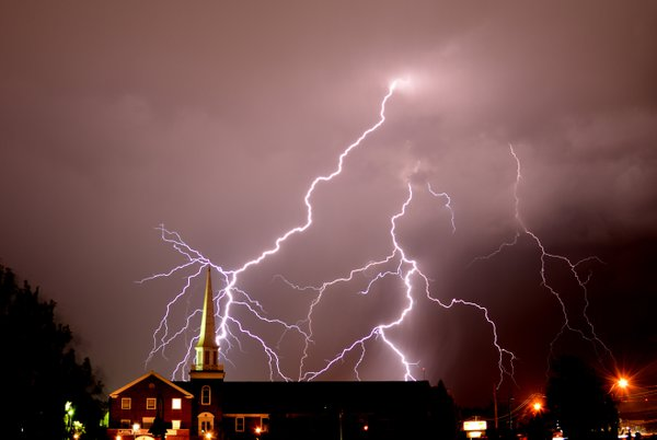Multiple bolts of lightning in the evening sky appearing behind a church building in West Virginia US thumbnail
