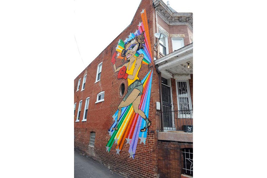 Side view of a brick rowhouse, with a colorful mural of a Black girl boxing with rainbows shooting from behind, spanning almost the whole height of the building.