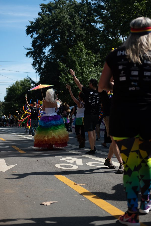 A woman in a rainbow dress with a parasol marches in Atlanta's pride parade. thumbnail