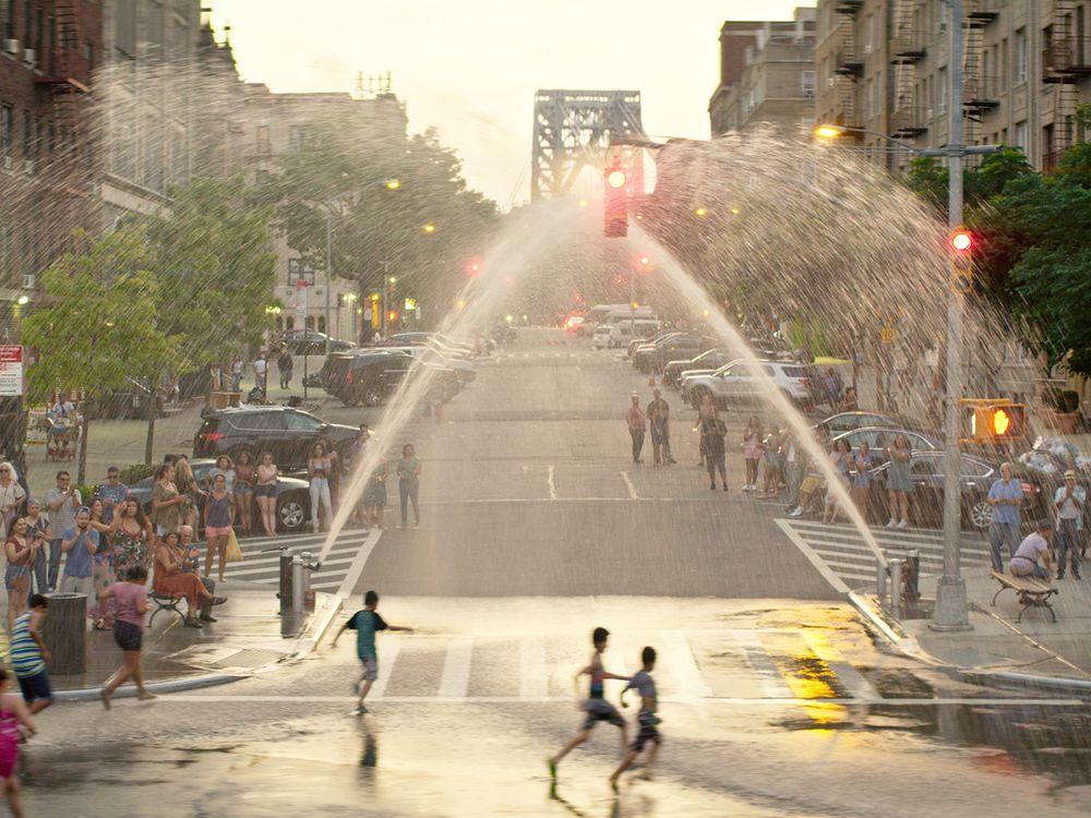 Children run through sprinklers in Washington Heights