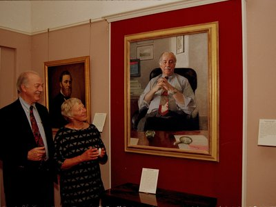 """Secretary Adams and his wife Ruth contemplate his official portrait, which to this day resides at the Smithsonian Institution """"Castle"""" Building."""