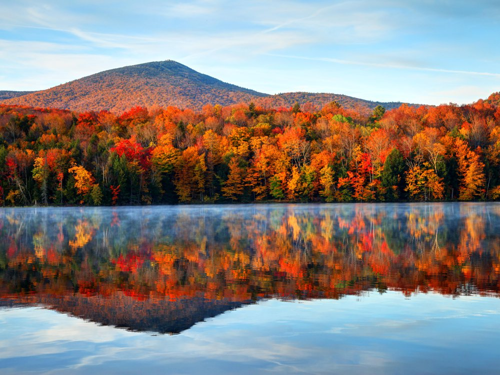 A lake, with a distant sloping hill and brilliant and orange red trees reflected perfectly in the still water. Overhead, a blue sky with wispy white clouds