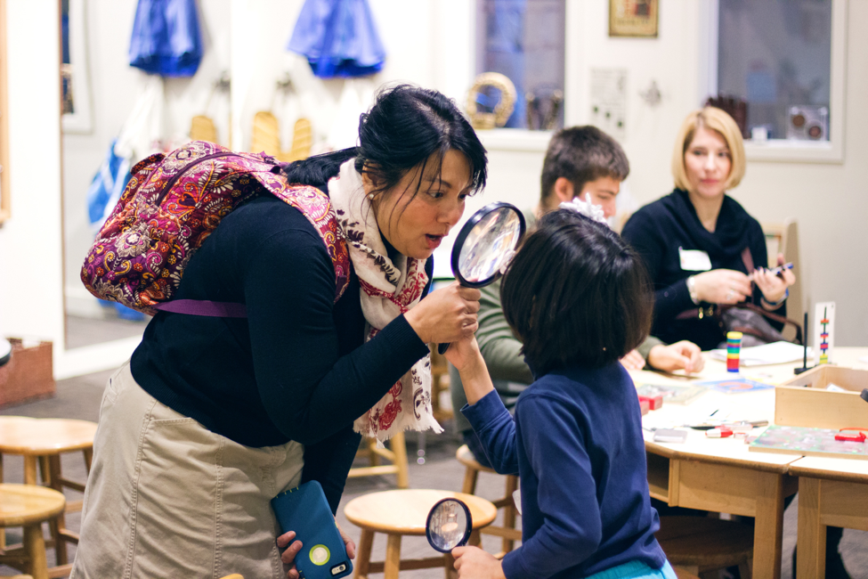 A mother and child look at each other through a magnifying glass.