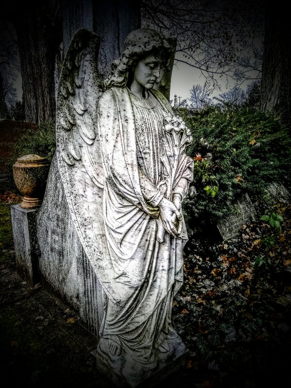 An Angel stand at the entrance as a monument to a plot in Grove Street Cemetery New London Ohio thumbnail