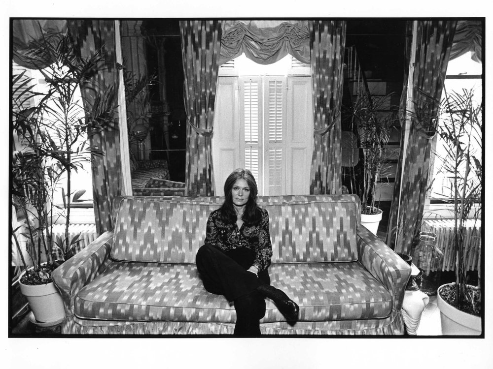 A black and white image of Steinem, a white woman in a patterned button down and black pants, sitting on a patterned couch in front of house plants and tall windows with curtains