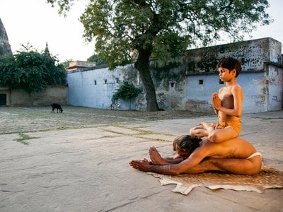 A man stretches into a west-facing extension known as paschimattanasana with his son perched on his back in padmasana, or lotus pose | Varanasi